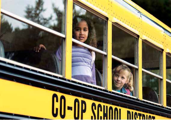 Children peer with curiosity out of a school bus. Of all the forms of local government in the United States, school districts are often the ones that draw the most attention from the public.