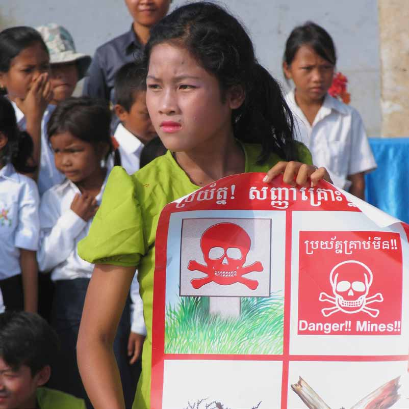 A member of a performing troupe doing mine risk education in Cambodia holds a poster showing different signs that warn of the