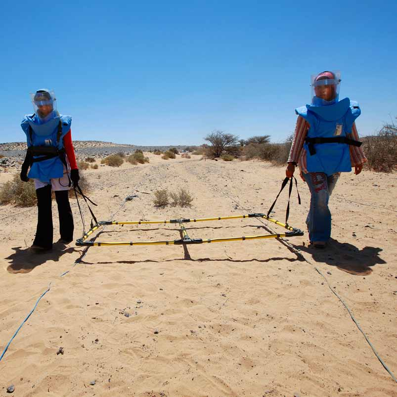 Taufa Ibrahim and Mariam Zaid, two female battle area clearance operators using a large loop detector in Mehaires, Western Sahara.