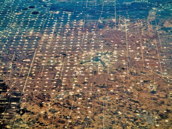Photo: Dennis Dimick/Flickr. A grid of drilling sites and roads, similar to those used in fracking, lies across the landscape near Odessa, Texas.