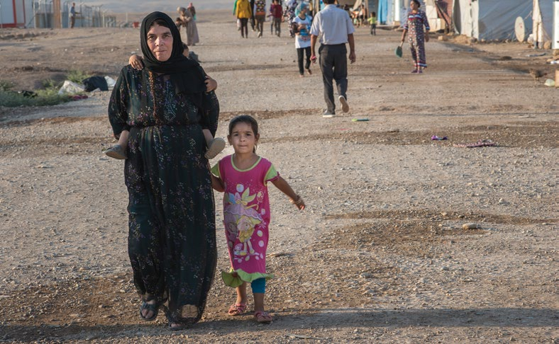 ABOVE: A Syrian refugee walks her grandchild in the streets of Domiz camp, Iraq.