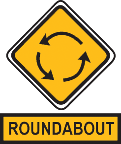 Slow down as required by the speed restriction sign and follow the road rules for roundabouts.