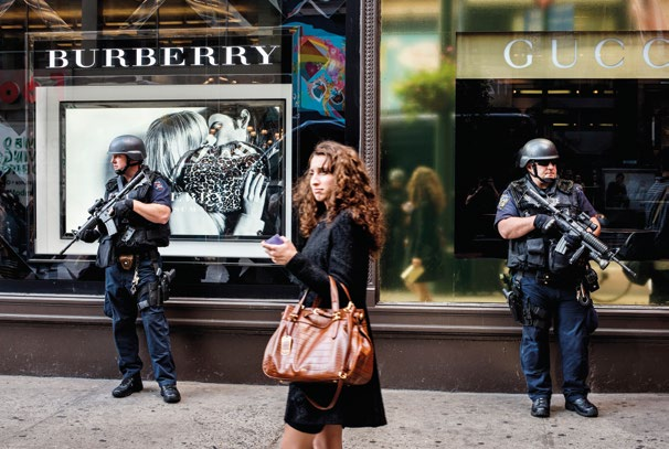EXTREME INEQUALITY 1.2 A woman walks past two heavily armed policemen on guard outside a department store in Manhattan (2008).