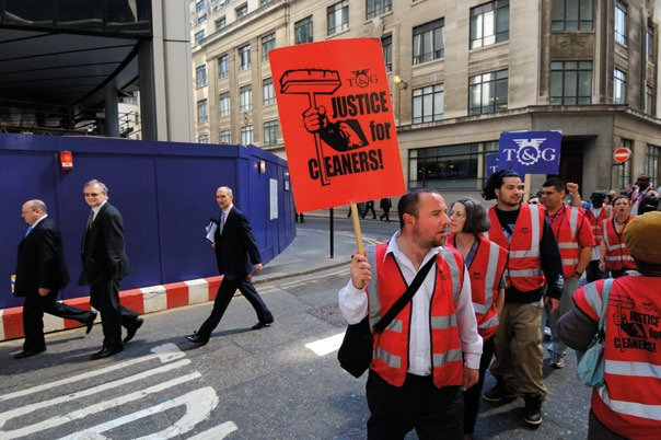 WHAT CAN BE DONE 2.2 Businessmen pass an official union demonstration against low wages and lack of benefits for cleaners in the City. London, UK (2007).