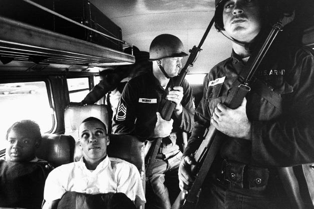 Freedom Riders traveling from Montgomery, Alabama, to Jackson, Mississippi, are escorted by National Guardsmen with bayonets at the ready. Over 20 additional Freedom Riders are behind the guardsmen.