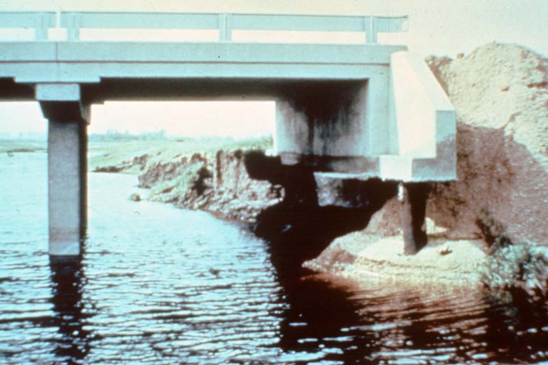 Abutment failures and erosion of the roadway embankment fill also occur from the action of the downstream wake vortex.