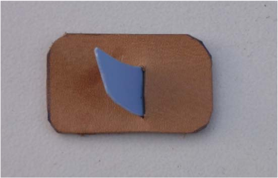 3 Cut a small piece of double sided sticky tape and stick the back of the plastic arrow rest to the back of the piece of leather, as shown in illustration 6.3.4.