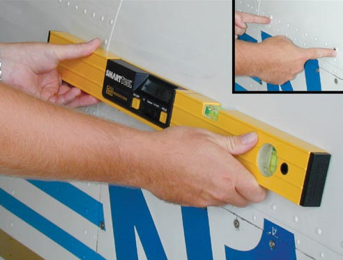 Figure 4-16. Spirit level being used on a Mooney M20. Figure 4-17. Plumb bob dropped from a wing leading edge.