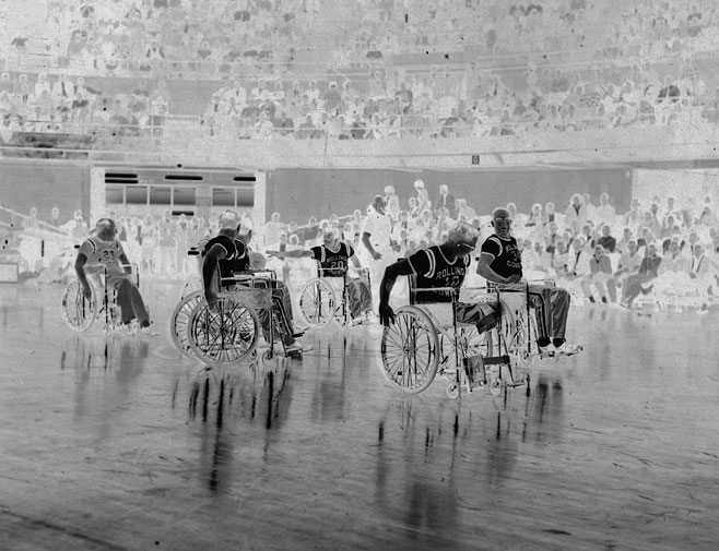 Frank Haraway and other men playing wheelchair basketball during