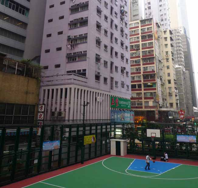 This basketball court, located in the middle of the street area, is squeezed tightly into the dense urban