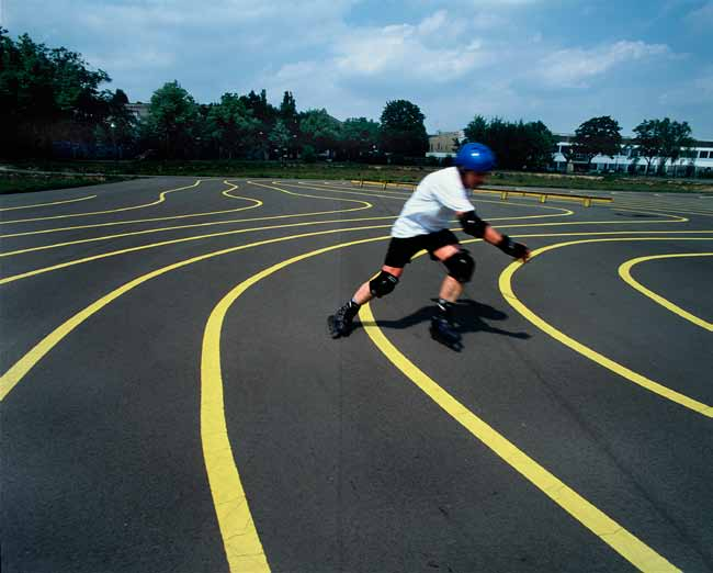 Recommendations Sweeping yellow lines have been painted on the asphalt surface, creating a wavy landscape and an almost topographical effect.