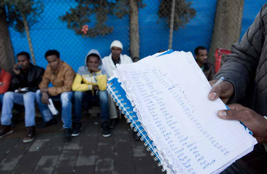 Sub-Saharan African nationals wait outside Israeli Interior Ministry offices in Tel Aviv on March 13, 2014 to renew their conditional release permits.