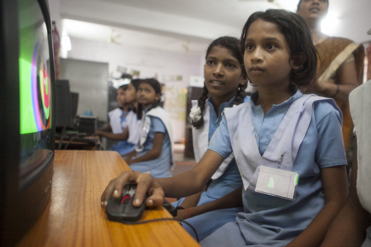School girls in Rajasthan, India learn to use the computer during an activity class.