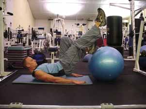 From the bridge position with feet on the stability ball, raise one leg 6 inches off the ball and curl the opposite leg in by