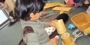Heuristic Play offering a group of children, for a defined period of time in a controlled environment, a large number of different kinds of objects and receptacles with which they play freely without