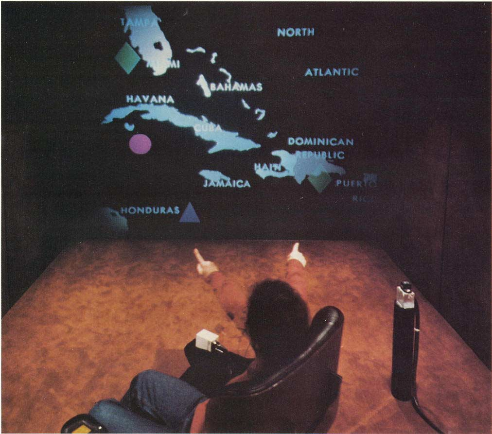 Figure 2 Talking and pointing to items on the Media Room's large screen. Here, the items are circle and diamond shapes being moved about against a backdrop of a Caribbean map.