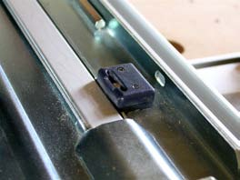 The green line is a strip of slippery plastic that makes the saw glide easily along the surface of the guide rail. The black plastic fitting is an adjustable gib, shown in close up here.