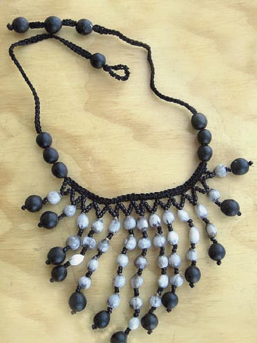 Necklace made of Canna edulis (small black seeds) with macaw and parakeet feathers. Figure 4. Necklace made of Sapindus saponaria (large black seeds) and Coix lacryma-jobi (whitish seeds).