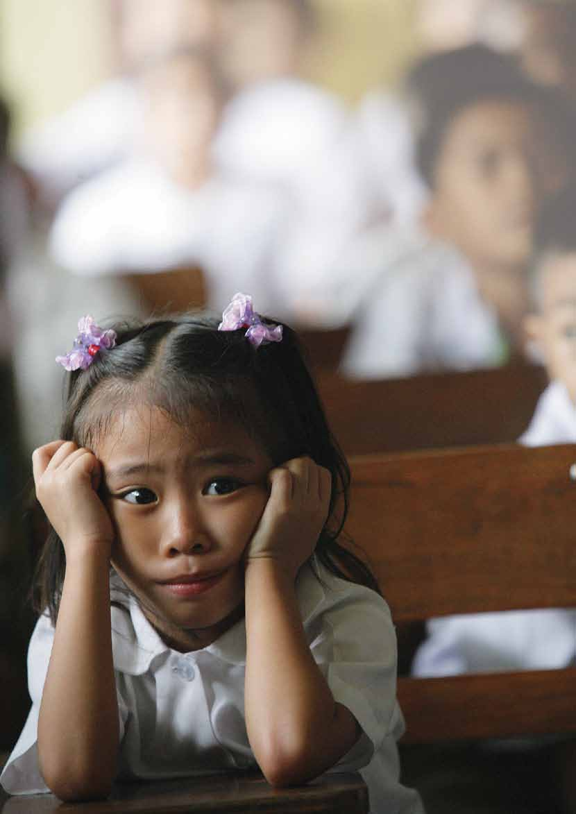 UNICEF/NYHQ2006-1468/Pirozzi A girl watches a video called 'Happy Tales' at Rosauro Almario Primary School in Tondo, a neighbourhood of Manila, the capital of the Philippines to promotes