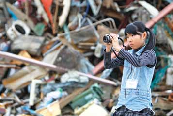139 Industrialized Countries Yuuna Sasaki, 8, photographs Kobuchi Beach, in the city of Ishinomaki in Japan, with debris towers behind her.
