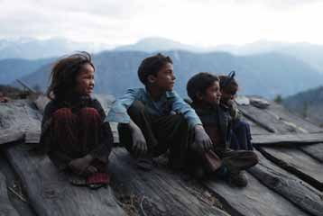 183 South Asia Children sit on a rooftop, watching the approach of a storm, in Sawa Khola Village, Mugu District of Nepal.