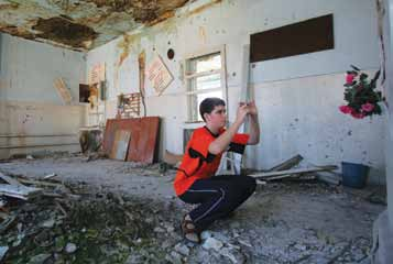 75 Central and Eastern Europe and the Commonwealth of Independent States Aleksandr Pogrebnoy, 14, photographs the remains of his classroom in Beslan, Russia.