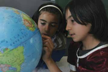 83 Central and Eastern Europe and the Commonwealth of Independent States Children examine a globe at their school in the village of Karaali in Ankara Province, Turkey.