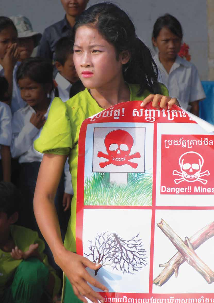 UNICEF/NYHQ2004-0763/Thomas A girl holds a poster showing different signs that warn of the presence of landmines, at Boeng Prolith Primary School near the western town of Pailin in Cambodia, as part