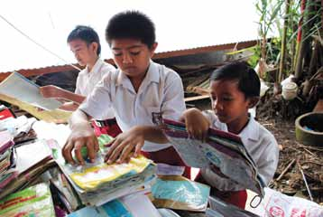 99 East Asia and the Pacific Boys sort through school books and salvaged educational materials at destroyed Elementary School 17 in Padang, Indonesia.