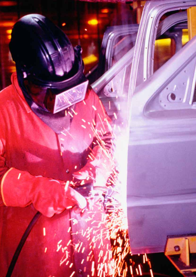 Welder working on car doors in an