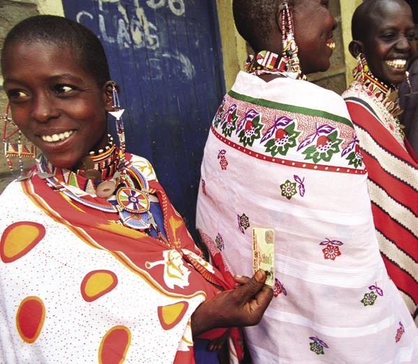 5 42 Masai women queue up outside a polling station in Kajiado district, holding their voting cards.