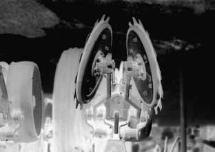 72 C.J. Baker Fig. 5.11. A pair of combined spiked discs and angled press wheels for covering no-tillage slots (from Baker et al., 1996).