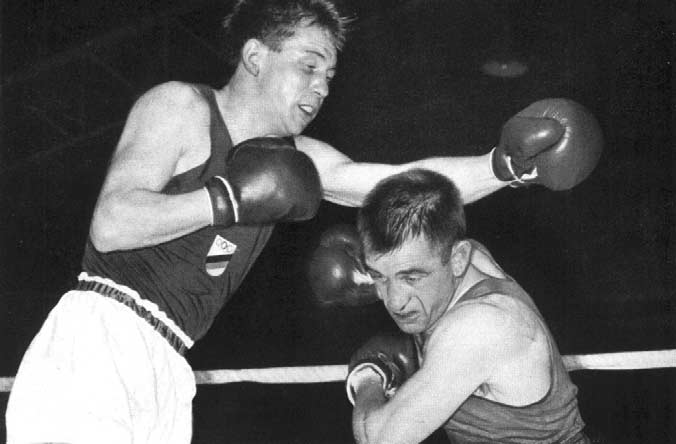 Byrne (right) of Ireland avoids a glancing left from Kurschat of Germany during their Lightweight fight. Middleweight.