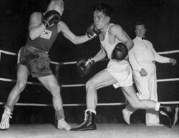 Bantamweight Silver Medallist, Song, scores in his match against Adela. FEATHERWEIGHT 90 908 90 9 98 9 96 98 9 (Up to 7 kg. lb. 0 oz. 9 dr.) Previous Olympic Winners L. O'Kirk R. Gunn P. Fritsch P.