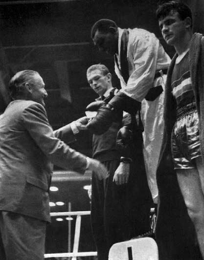 The Marquess of Exeter presents the medals in the Light-heavyweight class. Joint Bronze Medallist, Mouraouskas, is hidden behind Lucas (left). LIGHT 90 9 98 9 96 98 9 E. Eagan H. Mitchell V.