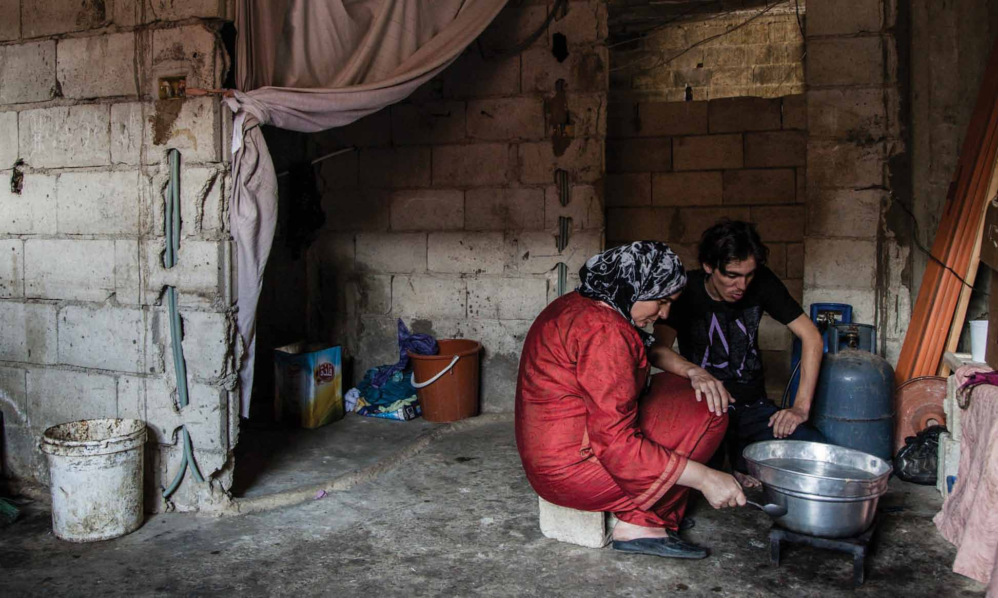 Khitan, a Syrian refugee woman, and her three sons (one shown in the picture) found shelter in an unfinished building in Tripoli, Lebanon with several other Syrian families.