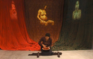upon which the video is projected: the central fabric/screen shows a pregnant woman, while the two side images are projections of the artist herself telling the stories of metaphorical queens.