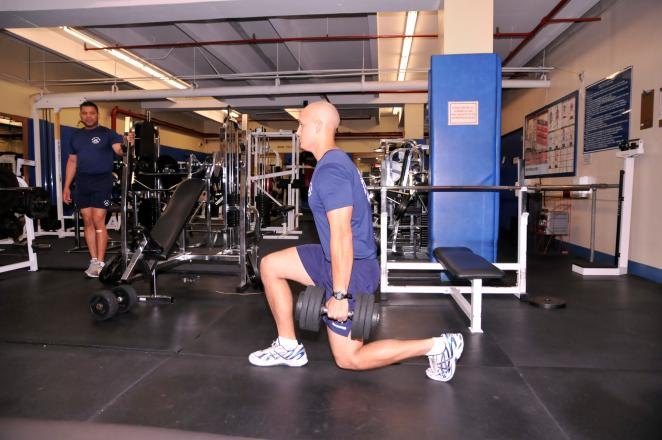 LUNGE TARGET AREA: UPPER LEG Hold dumbbells at arms length, palms facing in.