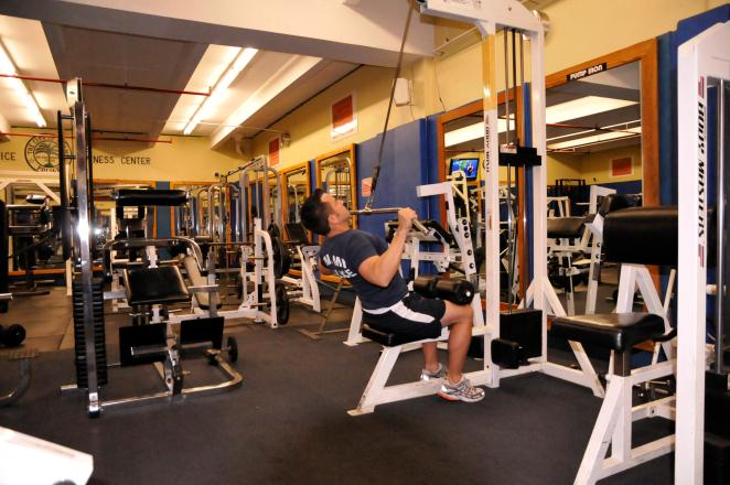 PULL-DOWN TARGET AREAS: BACK AND BICEPS Grasp bar with a medium to wide grip, palms facing away.