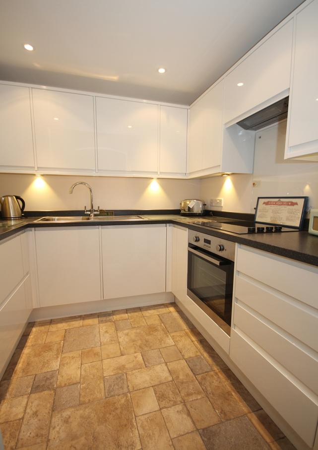 Kitchen 7' 11'' x 6' 10 (2.42m x 2.09m) Modern range of white high gloss fronted fitted wall and floor units with counter lighting and worktop surfaces.
