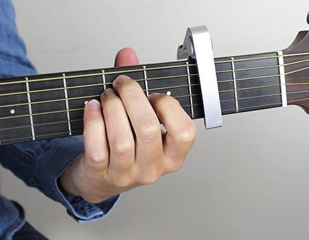 Want to play more chords easily? Get a capo A capo holds down the strings at a fret on your guitar. There are 3 reasons you should buy one; 1.