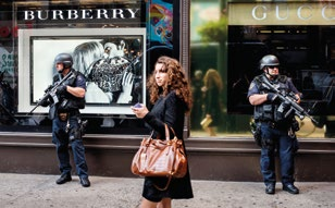 A woman walks past two heavily armed policemen on guard outside a department store in Manhattan (2008).