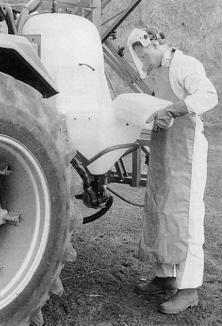 Safety and health in the use of agrochemicals Figure 33. A user wearing protective clothing and filling a pre-mix bowl on a crop sprayer Figure 35.