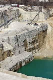 Q2. Limestone is used for statues and buildings. Limestone contains calcium carbonate (CaCO 3 ). (a) Figure shows a limestone quarry.