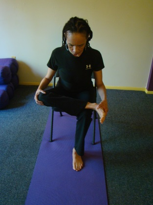 Outer Hip Stretch. Sitting in a chair, lift your right leg and place your right ankle over your left knee.