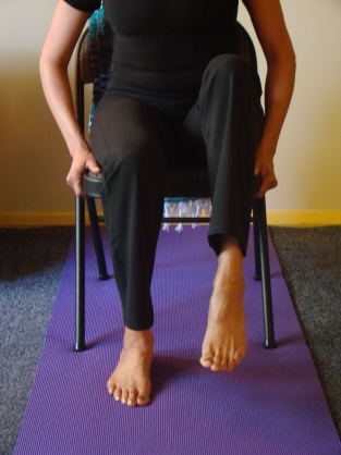 Inhale and then exhale and release the twist, sitting tall, facing forward. Repeat on the opposite (right) side. Ankle Stretch.