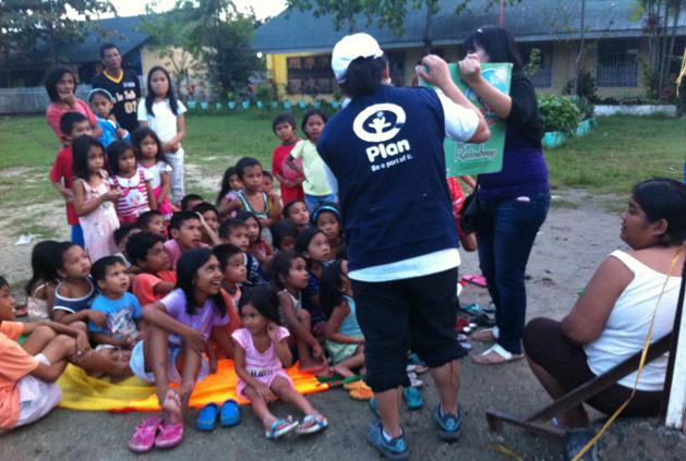 A Plan staff with a volunteer conducting storytelling session to children in the evacuation center in Cagayan de Oro in the Southern part of the Philippines.