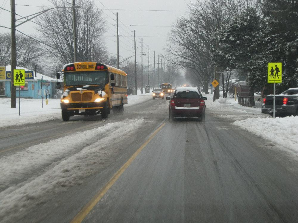 School bus producing a visibility obstruction at a school crossing area.