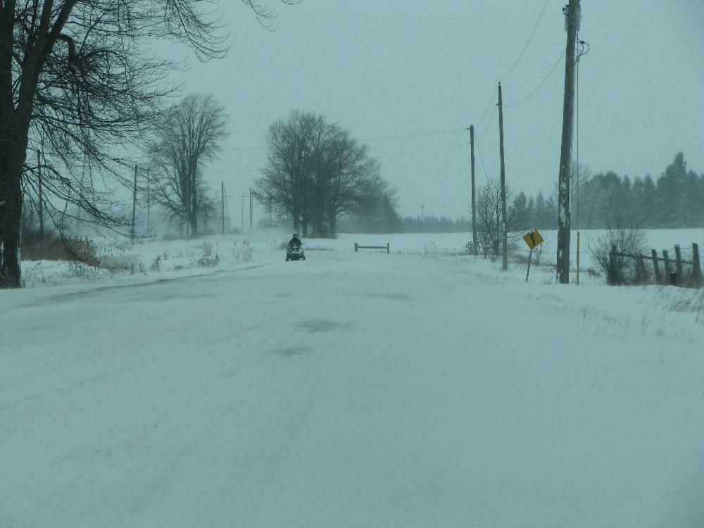 View of southbound snowmobile on Clarke Road northeast of London, Ontario Canada