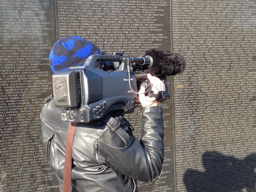 View of French camera man at wall monument to the fallen in the Vietnam war.
